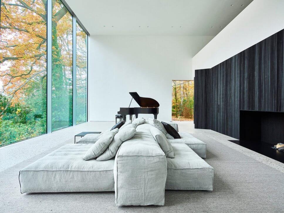 Wohnzimmer mit Sofa, Kamin und Flügel mit großen Fenstern