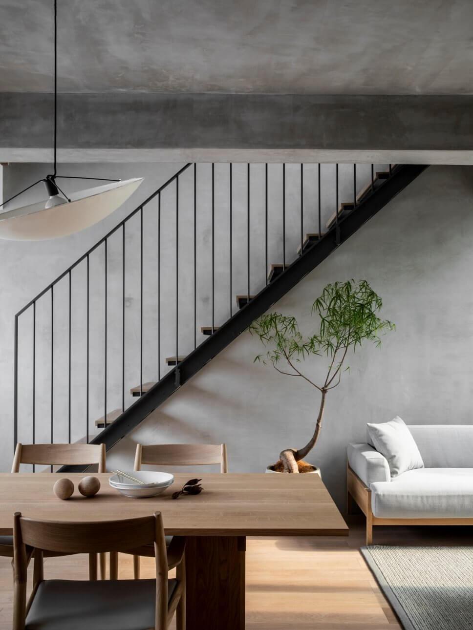 Japanisches Esszimmer mit Holztisch, Stühlen, Zimmerpflanze und Treppe