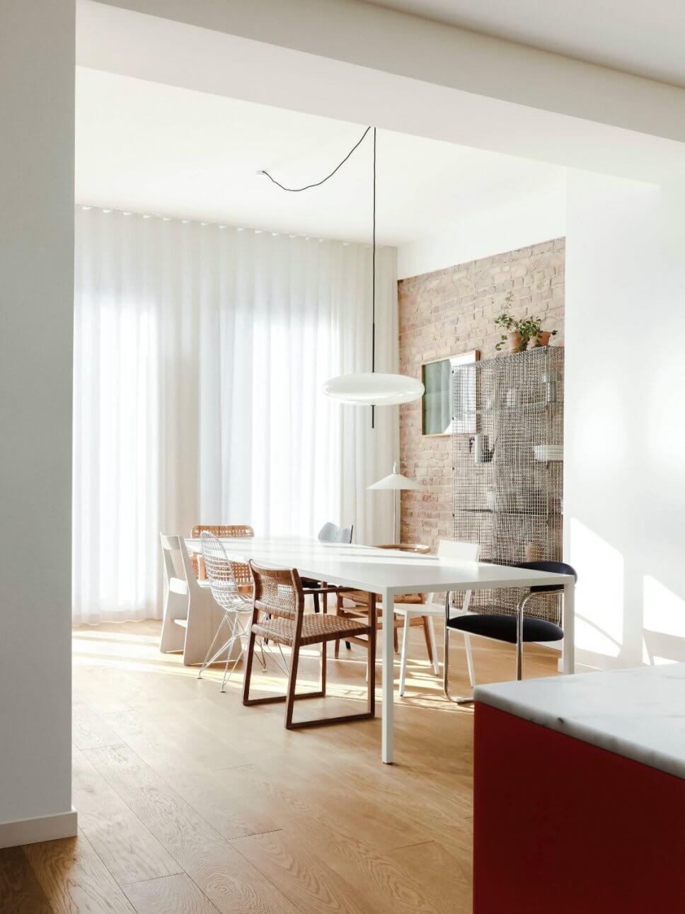 Modernes Esszimmer mit Backsteinwand, langem Tisch und unterschiedlichen Stühlen
