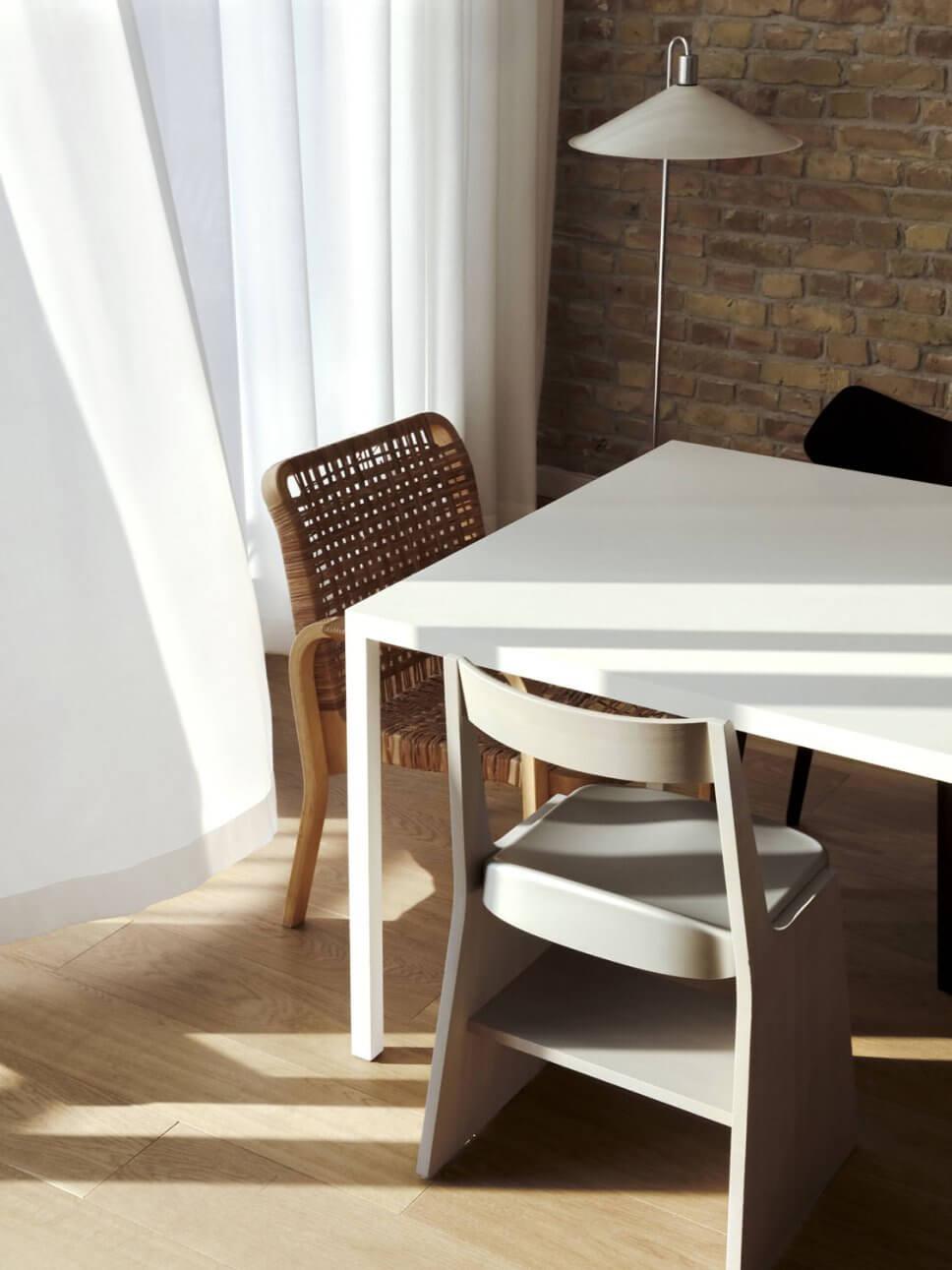 Modernes Esszimmer mit Backsteinwand, Esstisch und unterschiedlichen Stühlen