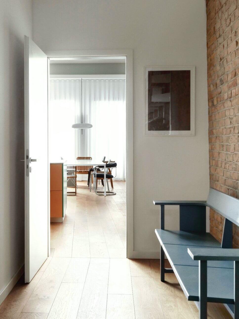 Moderne Wohnung mit Backsteinwand, Blick durch Tür von Flur ins Esszimmer