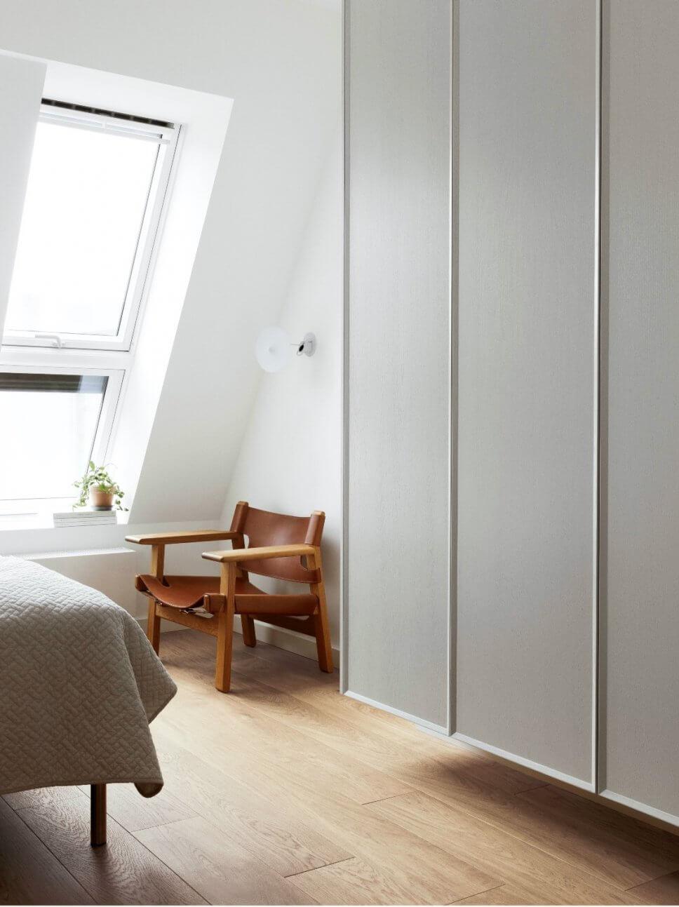 Modernes Schlafzimmer mit Dachschräge, Holzsessel und Kleiderschrank