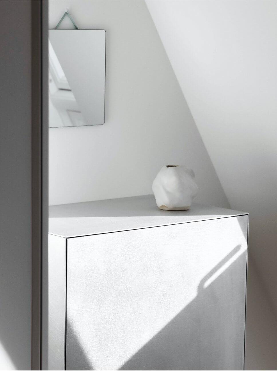 Kleiner Spiegel hängt über modernem Schrank