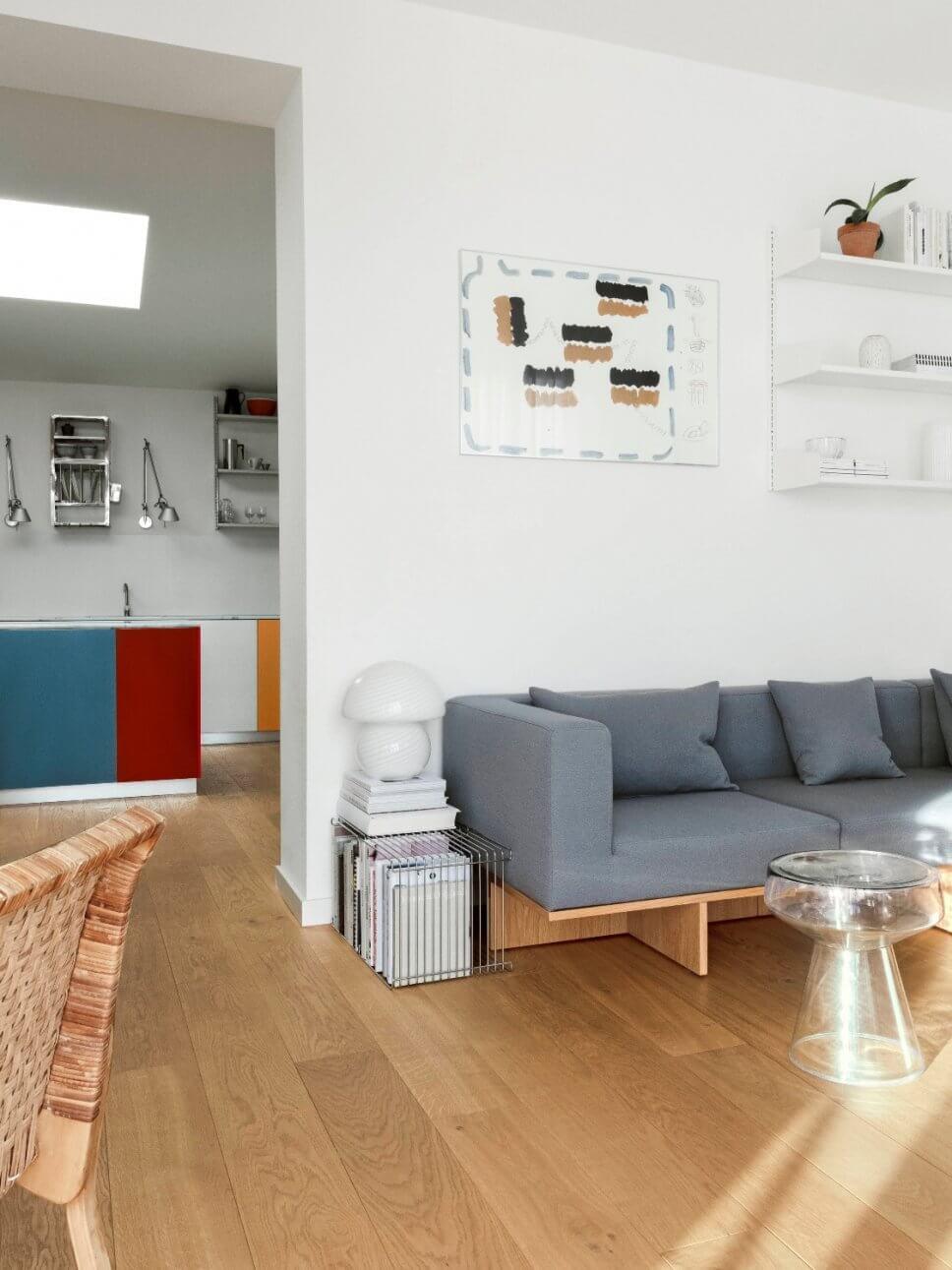 Modernes Wohnzimmer mit Sofa, Coffeetable und Blick in die Küche