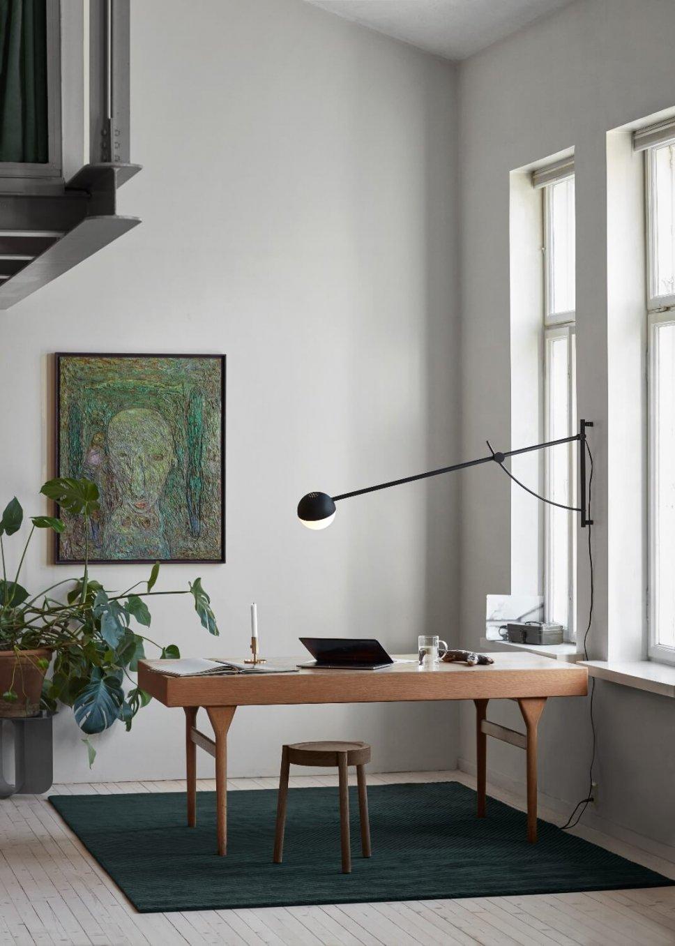 Moderne Wandleuchte hängt über Schreibtisch