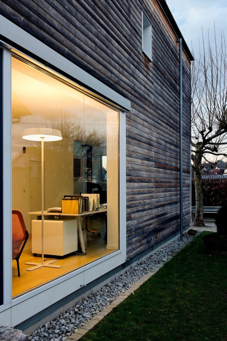 Blick durch ein Panoramafenster zeigt Home Office mit Stehleuchte