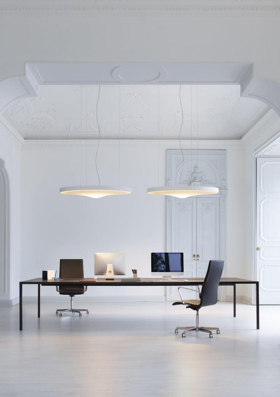 Zwei moderne Pendelleuchten hängen über Schreibtisch