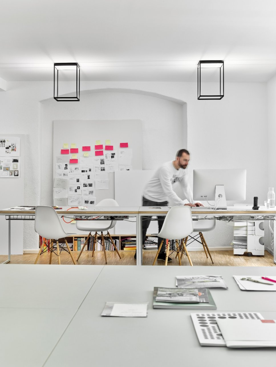 Zwei moderne Deckenleuchten hängen über Schreibtisch