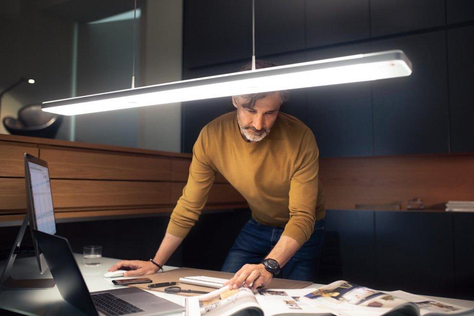 Moderne Pendelleuchte hängt über Schreibtisch, Mann arbeitet darunter