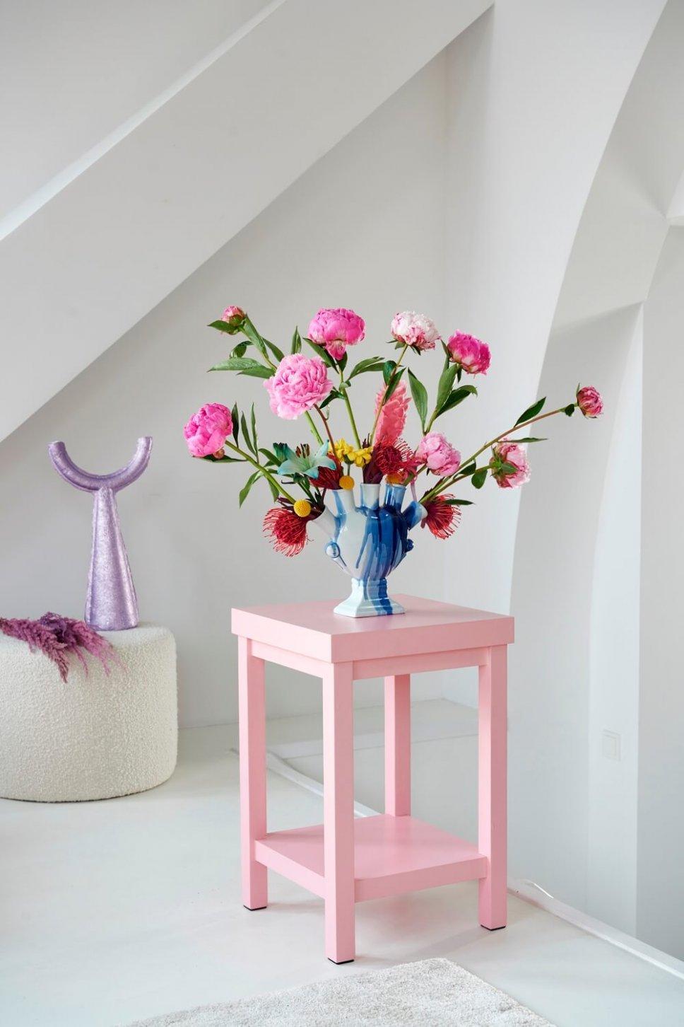 Moderner Wohnraum mit ausgefallener Vase, gefüllt mit Pfingstrosen