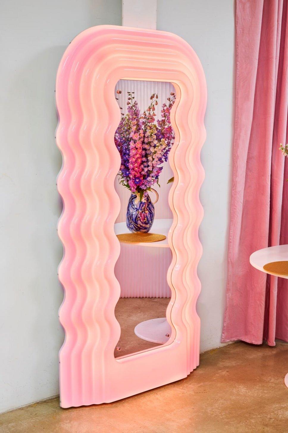 Rosa Standspiegel, in dem sich ein bunten Blumenstrauß spiegeln