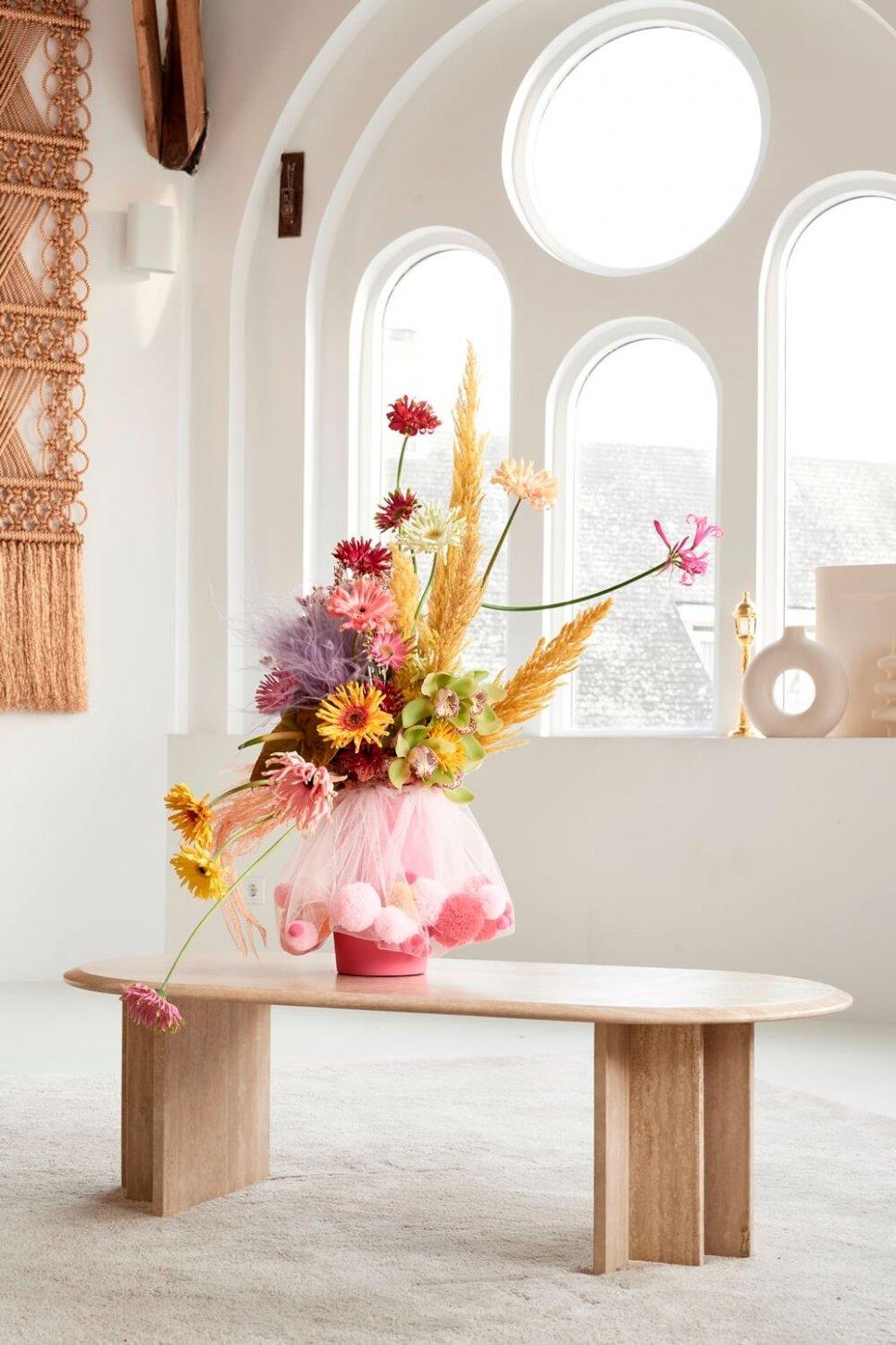 Moderner Wohnraum mit ausgefallener Vasen, gefüllt mit Gebera