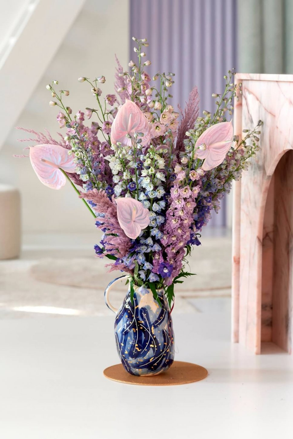 Moderner Wohnraum mit ausgefallener Vase, gefüllt mit Delphinium und Anthurien