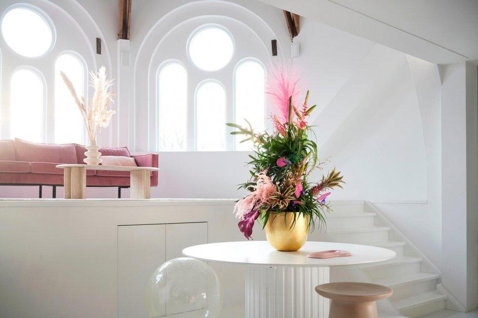 Moderner Wohnraum mit goldener Vasen, gefüllt mit Bromelie