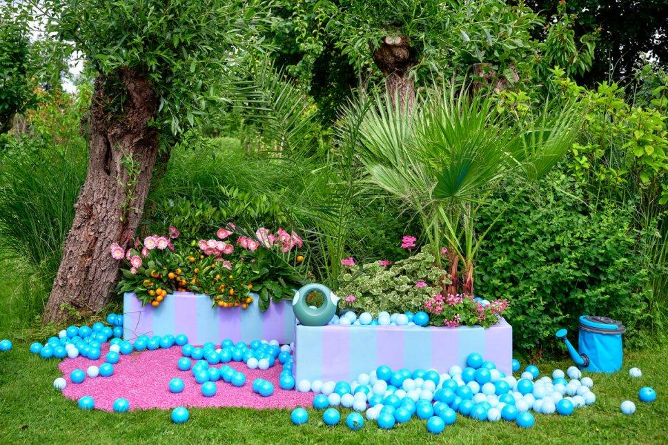 Garten mit bunten Blumenkasten gefüllt Gerbera, Zitruspflanzen, Pelargonien und Palmen