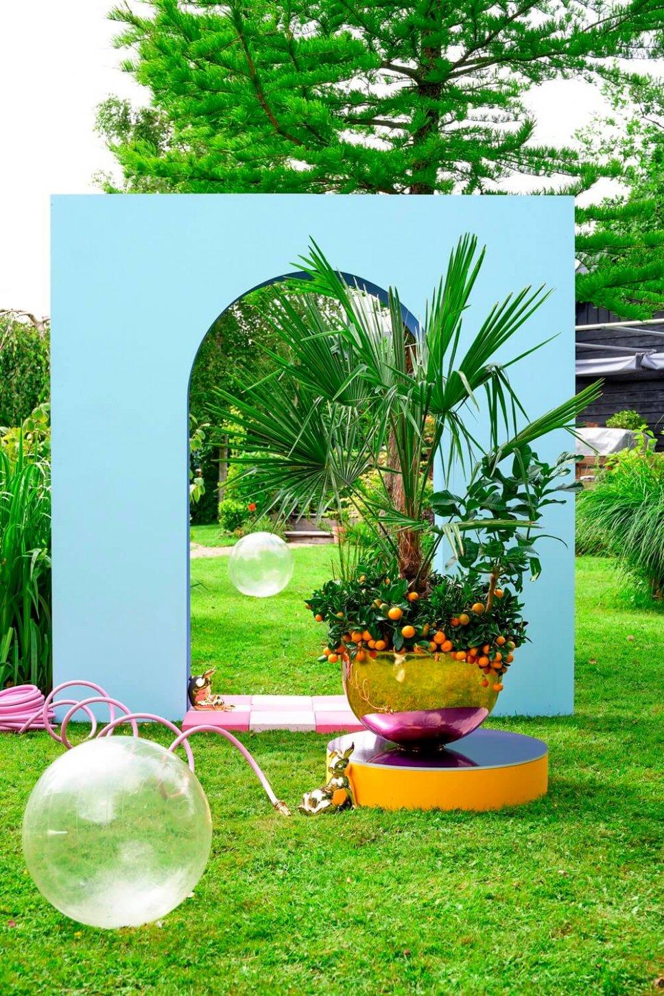 Garten mit verspiegeltem Blumenkasten gefüllt mit Zitruspflanzen und Palmen