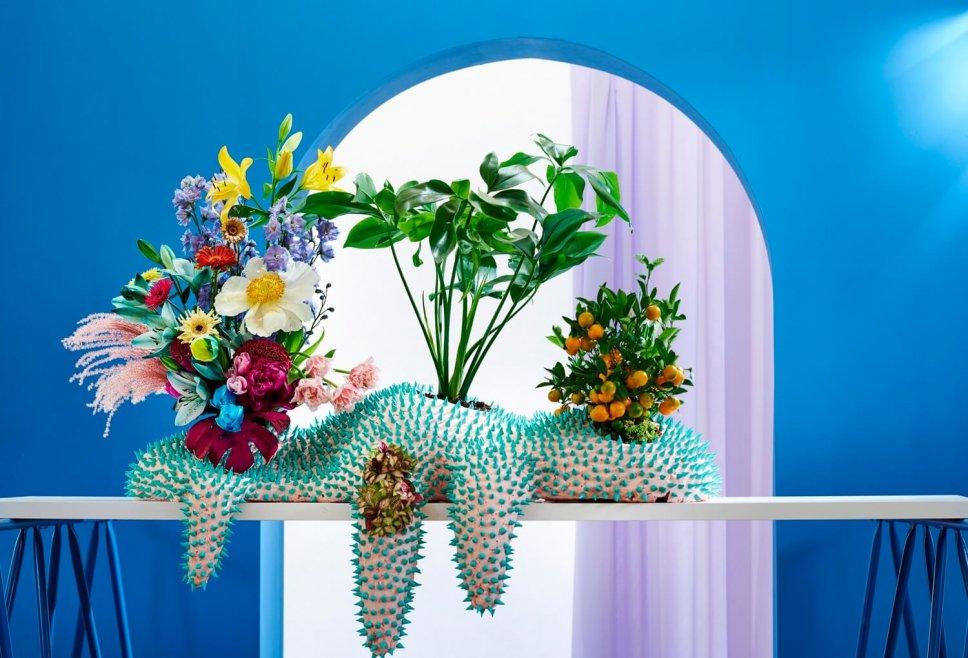 Schriller Blumenkasten gefüllt mit buntem Blumenstrauß und Zimmerpflanzen