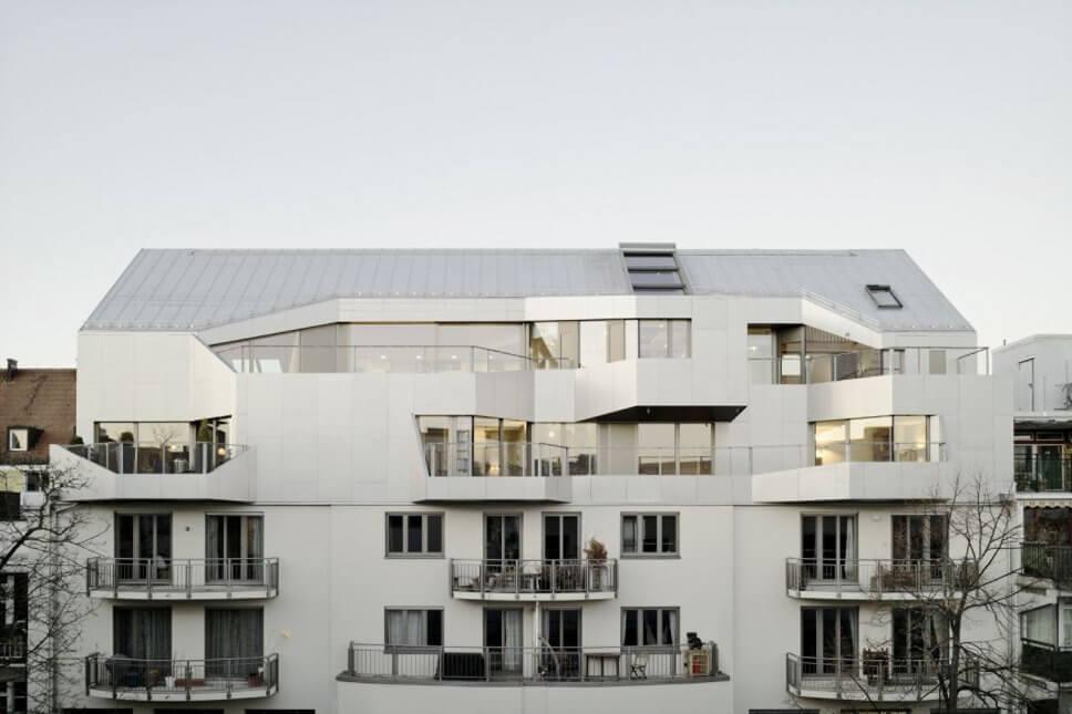 Mehrgeschossiges Haus von moderner Architektur mit vorgesetzten Balkonen und großen Fenstern