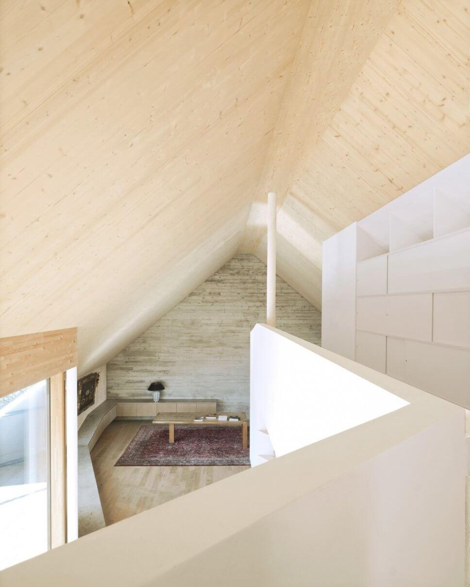 Moderner Wohnraum im Dachgeschoss mit großen Fenstern, Galerie und Sichtbetonwand