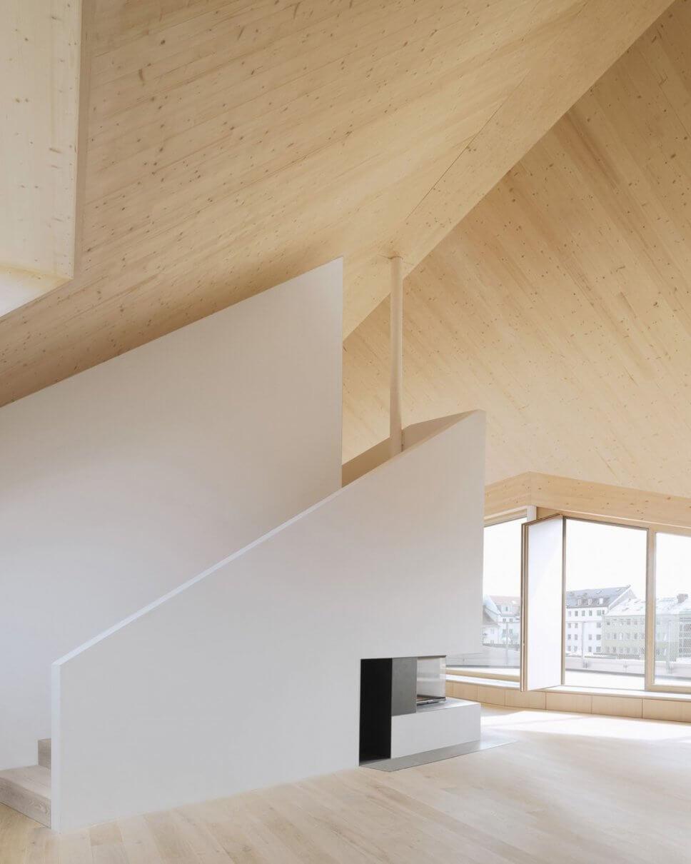 Moderner Wohnraum im Dachgeschoss mit großen Fenstern, Holzvertäfelung und Kamin
