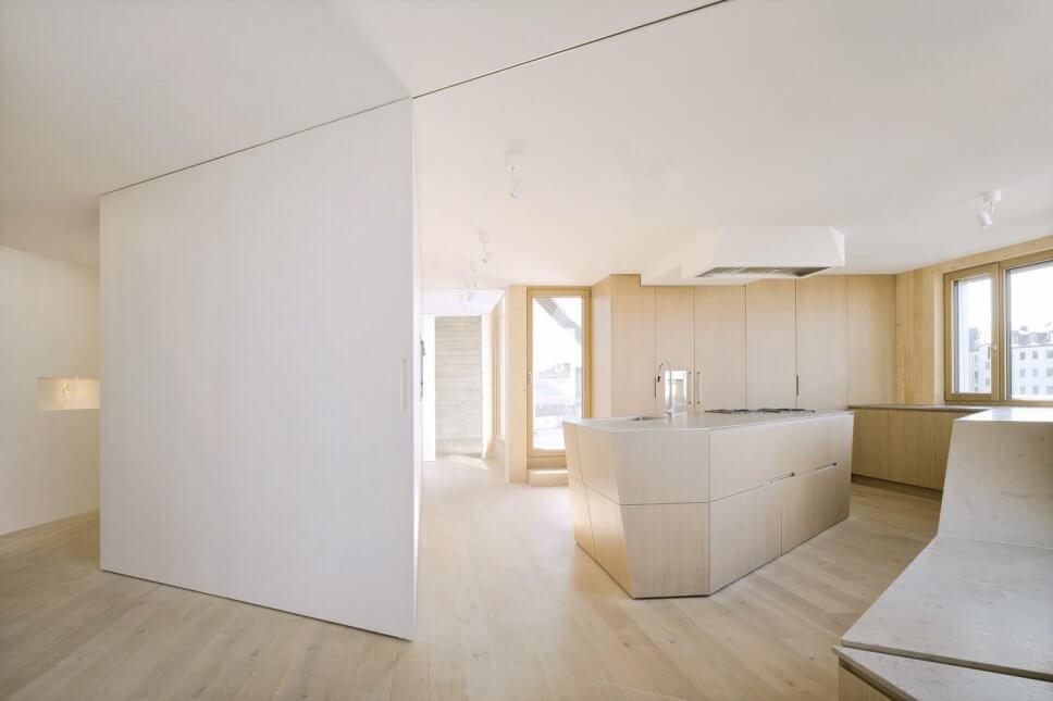 Moderne offene Küche im Dachgeschoss mit großen Fenstern, Holzvertäfelung