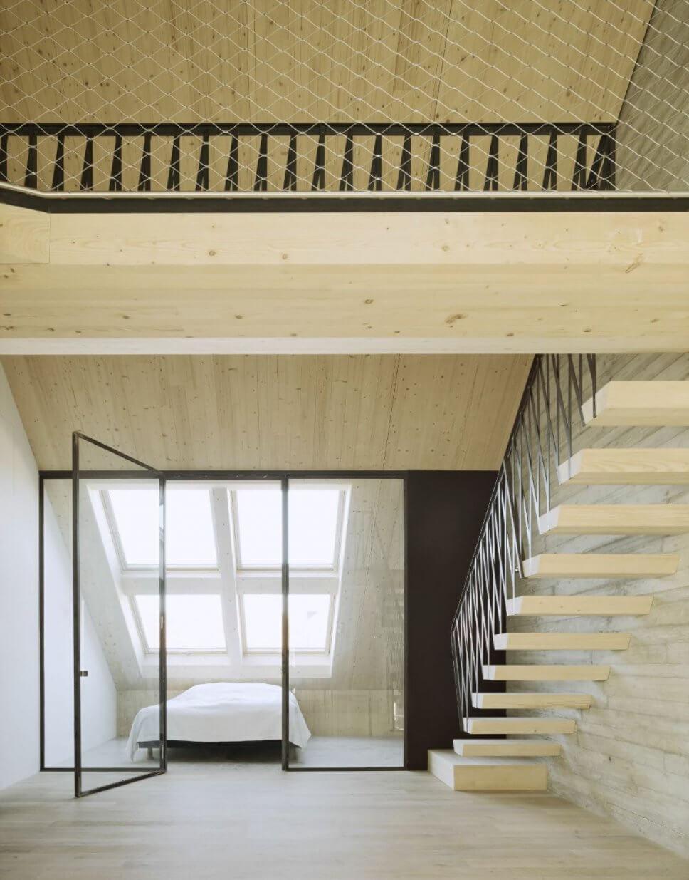 Modernes Schlafzimmer im Dachgeschoss mit Dachfenstern, Galerie, Holztreppe und Sichtbetonwand
