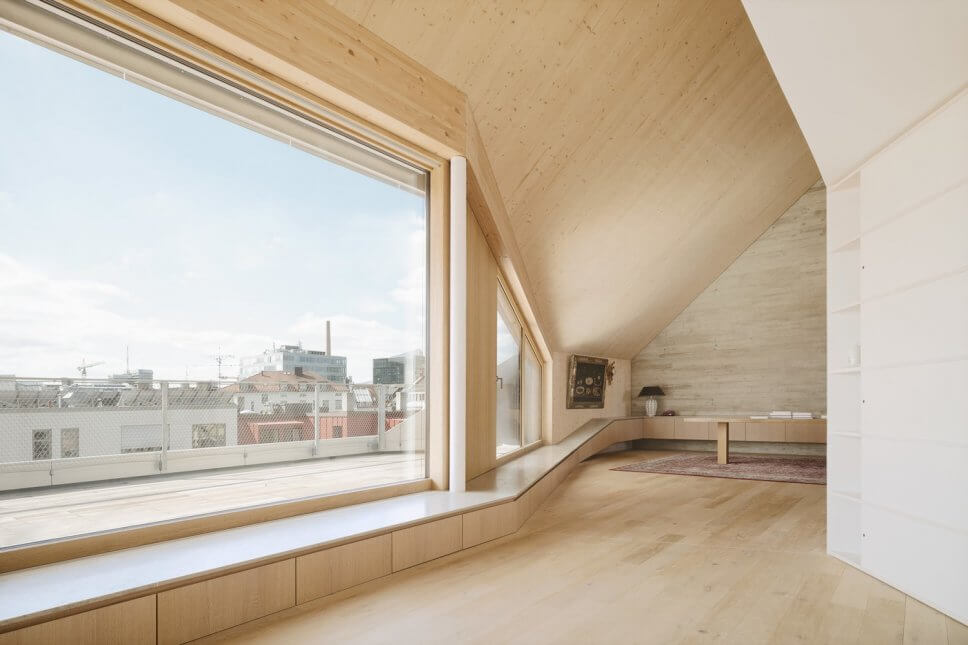 Moderner Wohnraum im Dachgeschoss mit großen Fenstern, Holz- und Sichtbetonwand