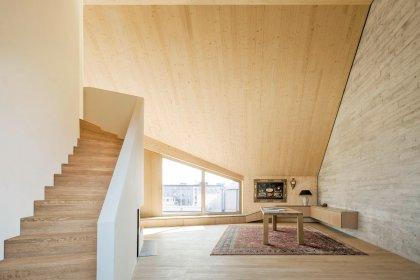 Moderner Wohnraum im Dachgeschoss mit großen Fenstern, Holztreppe und Sichtbetonwand