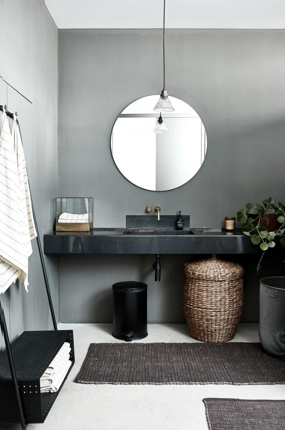 Schwarzer Waschtisch mit rundem Spiegel darüber