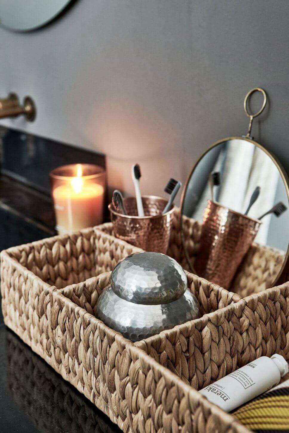 Korb mit Kupferbechern und Zahnbürsten im Badezimmer