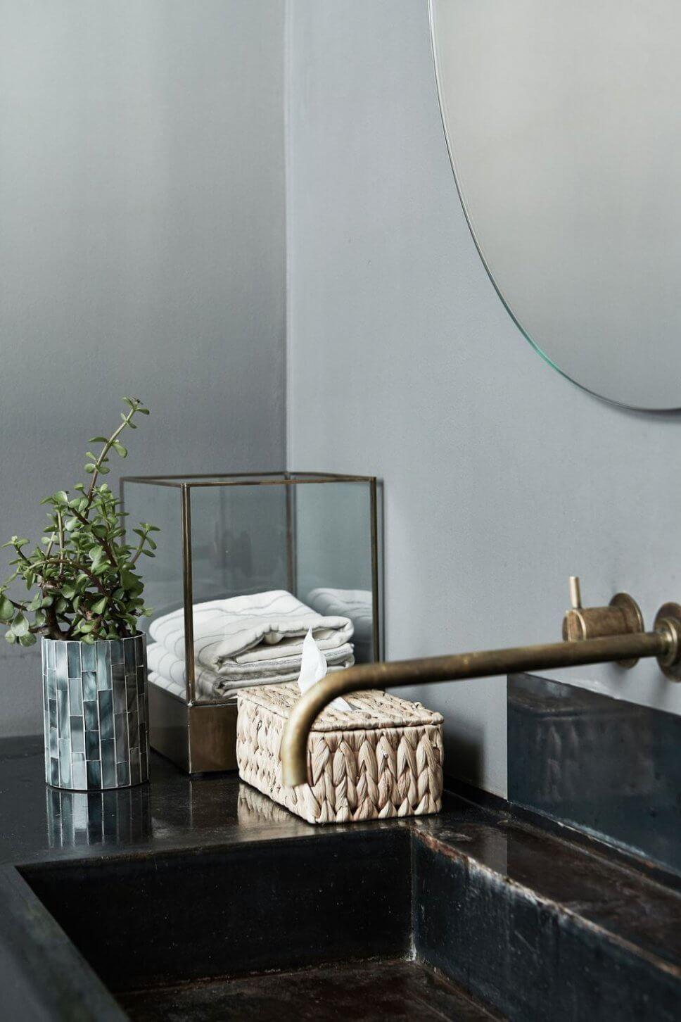 Glasvitrine mit Handtuch und Kosmetiktuchbox aus Korb auf Waschtisch