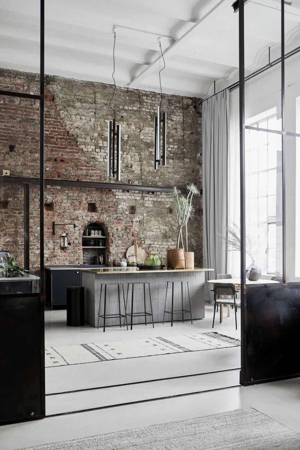 Blick durch hohe Stahlglastüren in offene Küche mit Backsteinwand