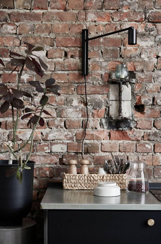 Wandlampe und Geschirr vor Backsteinwand