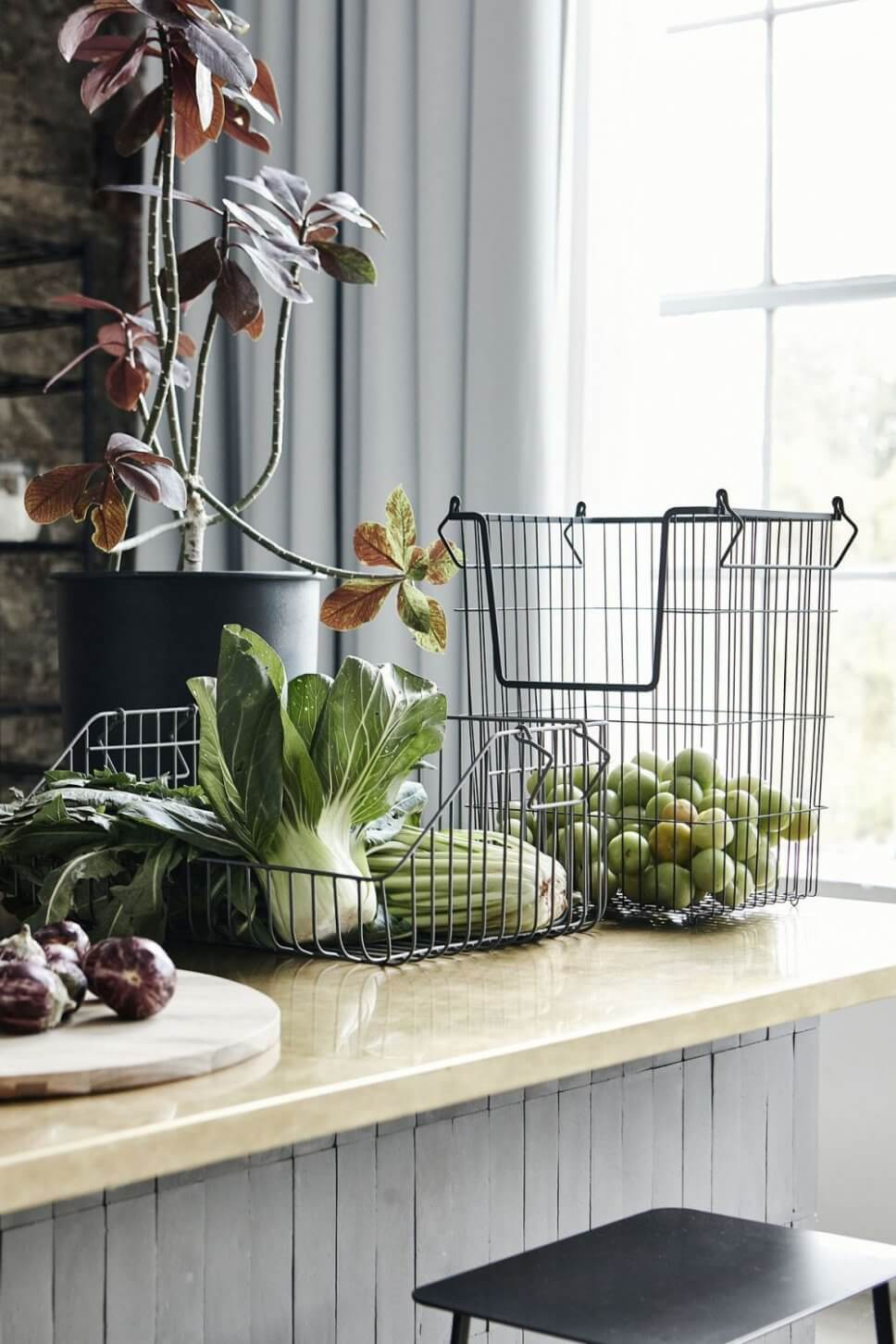 Gemüse und Obst in Drahtkörben auf Küchentresen