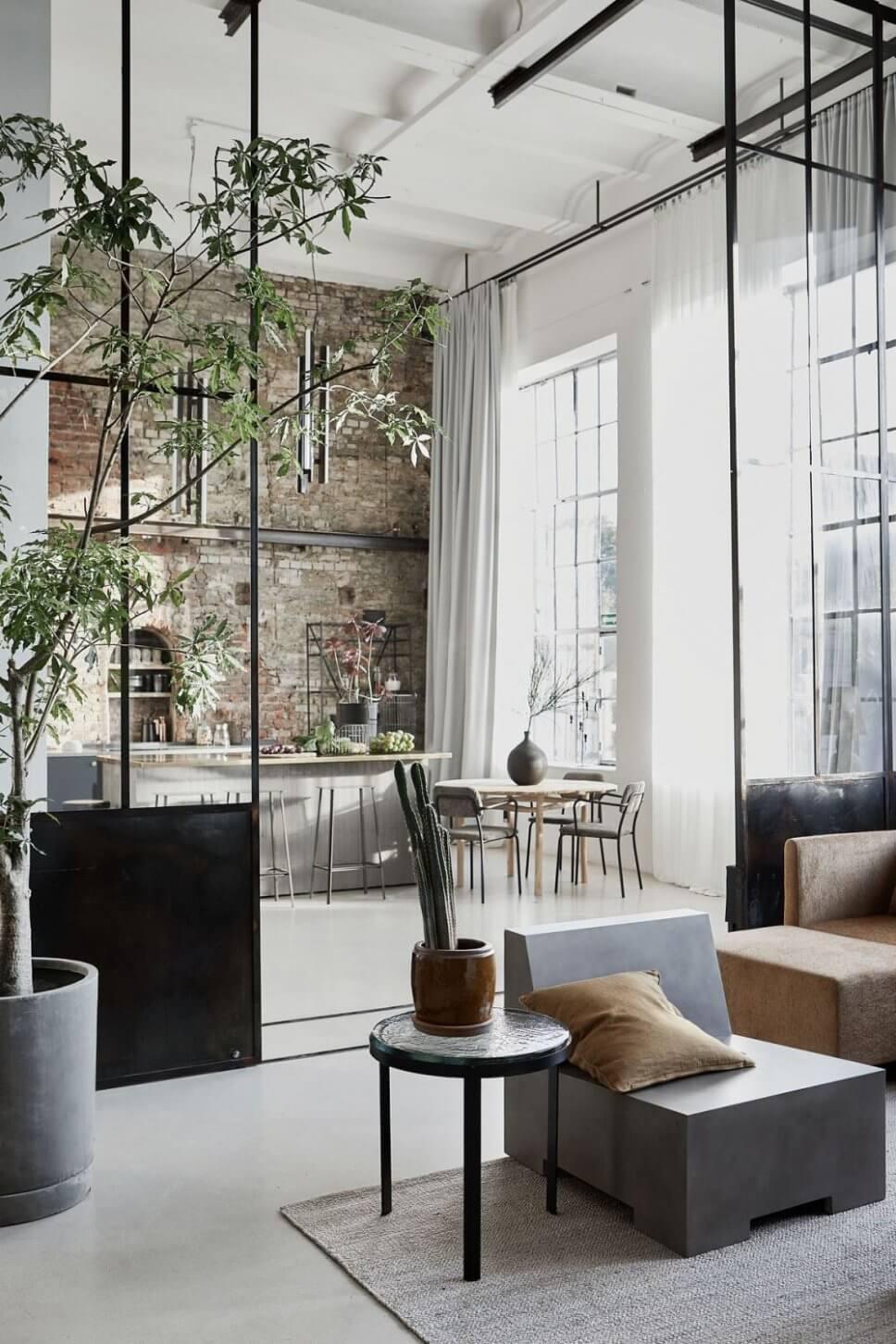 Sofas und Coffeetable im Industrieloft mit Blick durch hohe Stahlglastüren in offene Küche