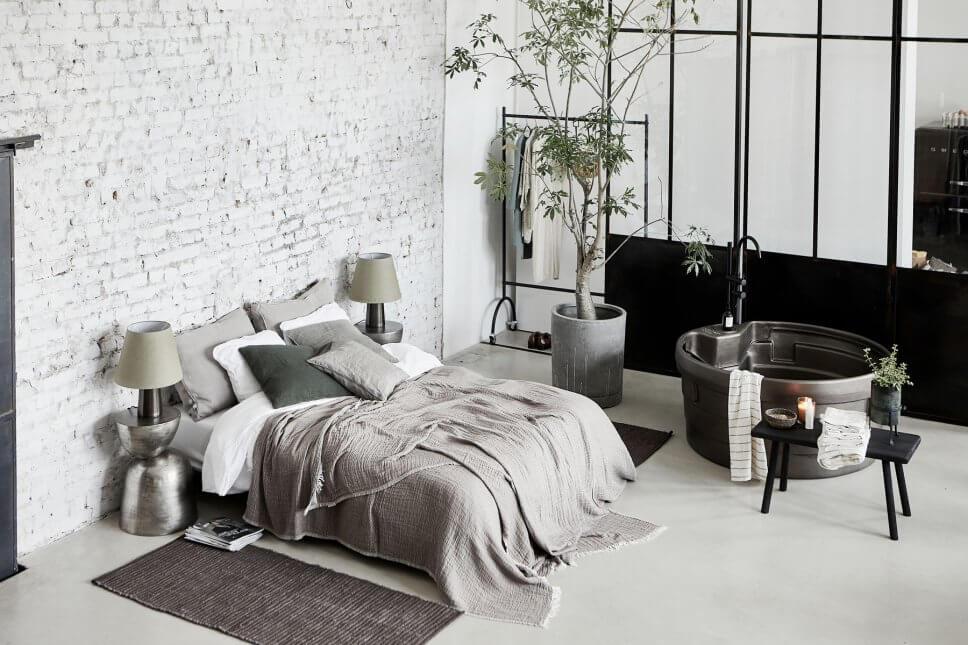 Bett vor Backsteinwand und freistehende Badewanne