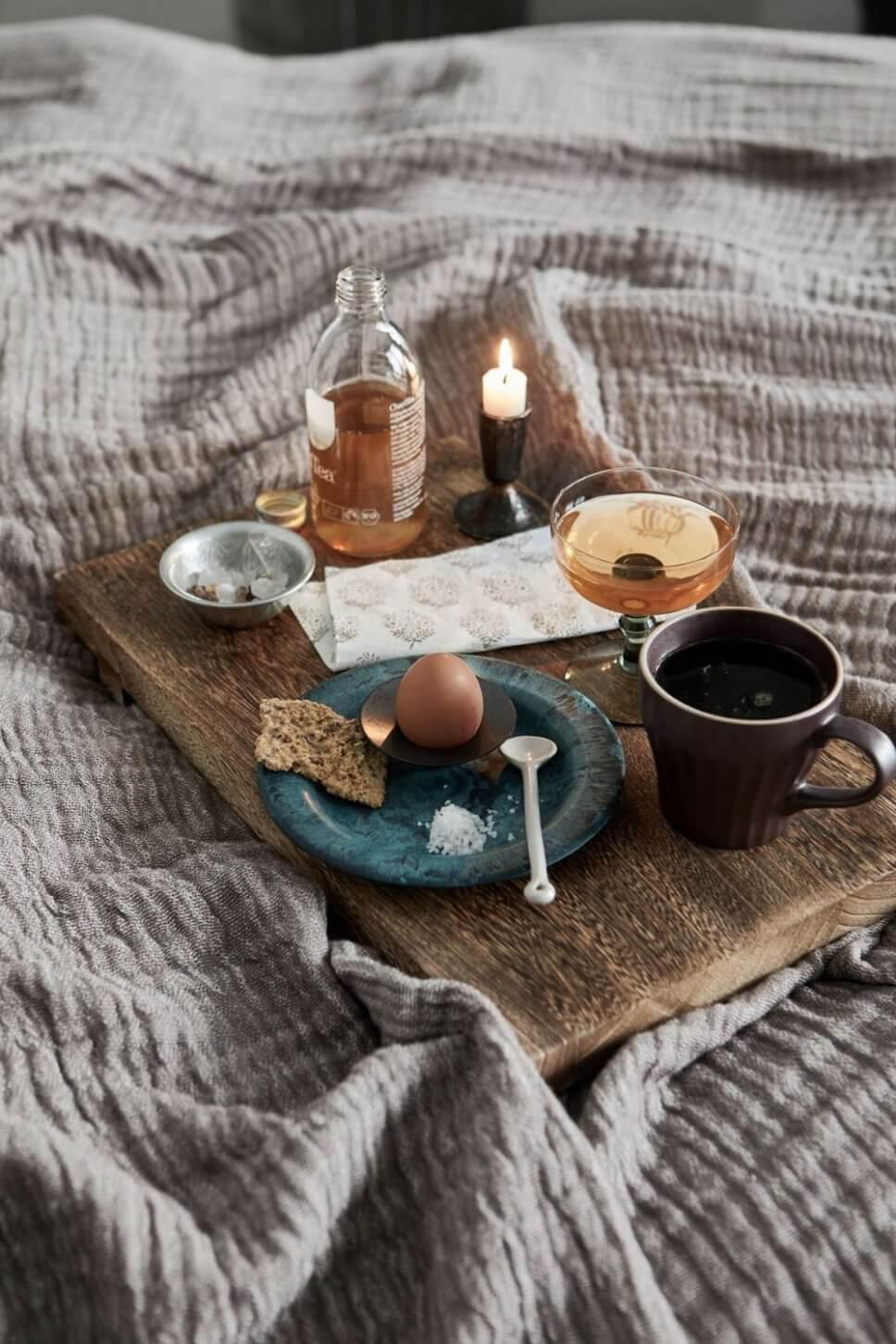 Holzbrett mit Teller und Frühstücksei sowie Kaffeebecher auf Bettdecke