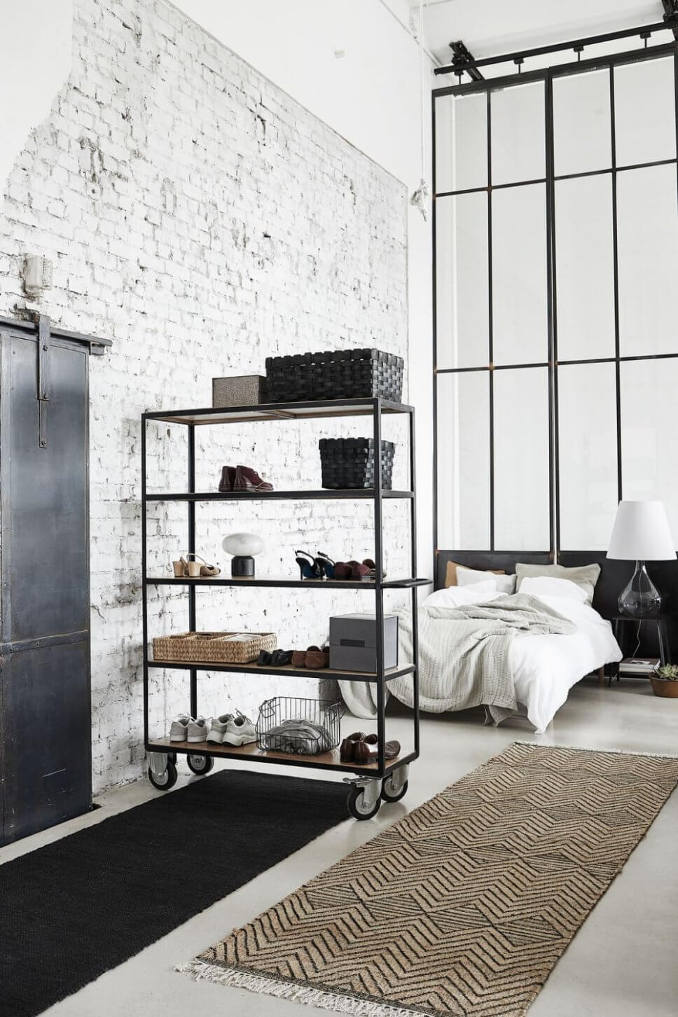 Stahlregal auf Rollen vor Bett neben Backsteinwand