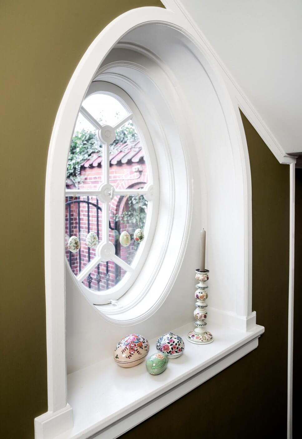 Ostereier hängen in rundem Altbaufenster, bemalte Holzeidosen liegen auf Fensterbank