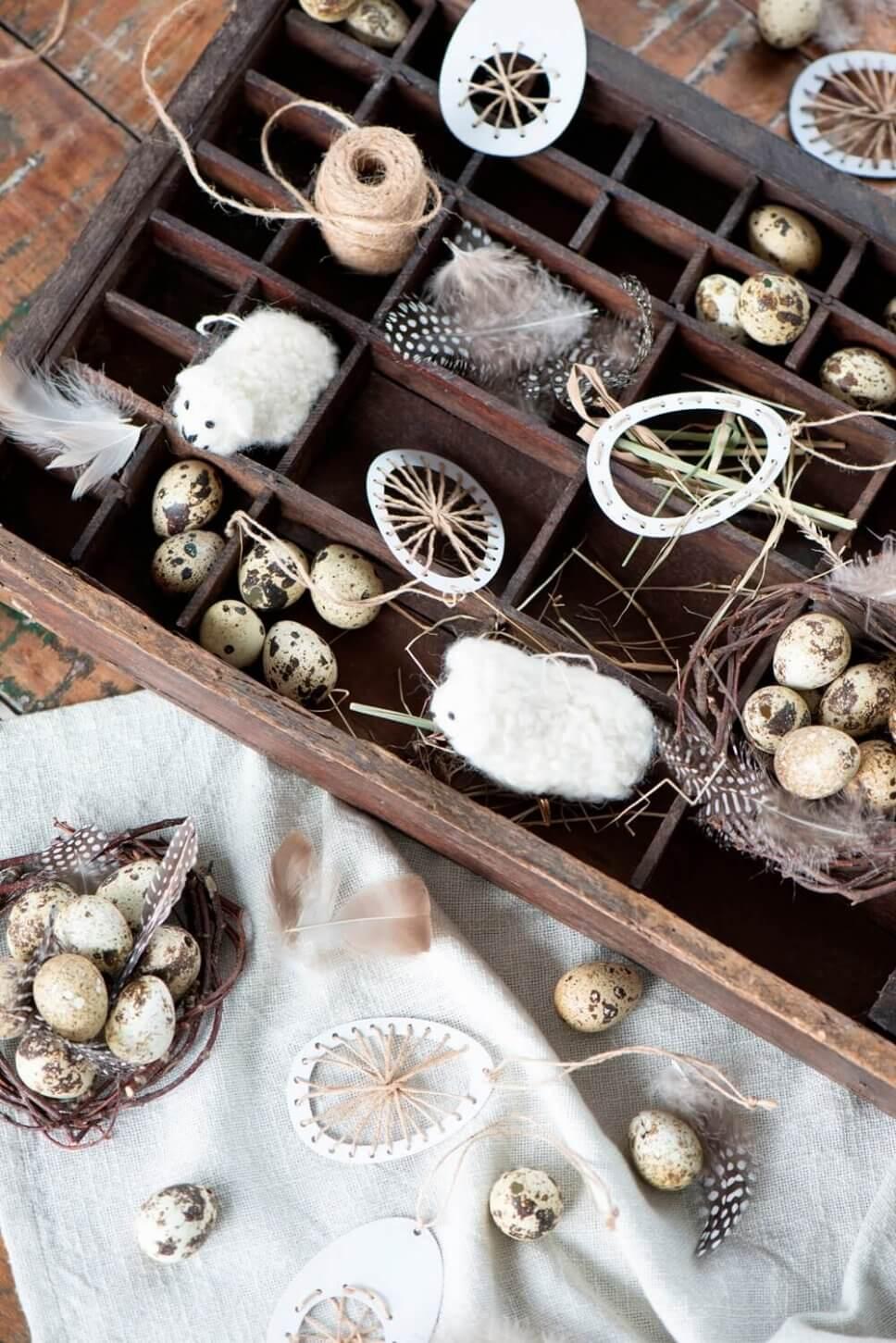 Wachteleier, Osterhänger und Wollschäfchen liegen im Setzkasten