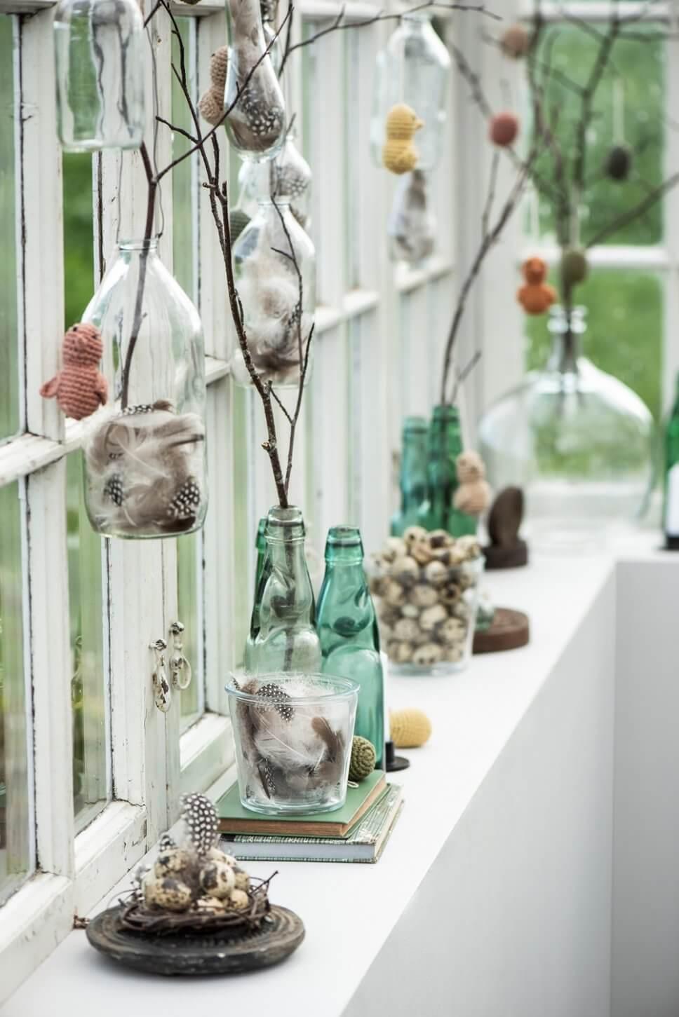 Gehäkelte Küken hängen an Zweigen in Flaschen auf Fensterbank