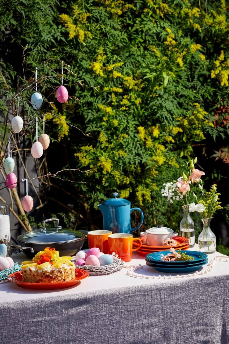 Österlich dekoriertes Buffet mit buntem Geschirr im Garten