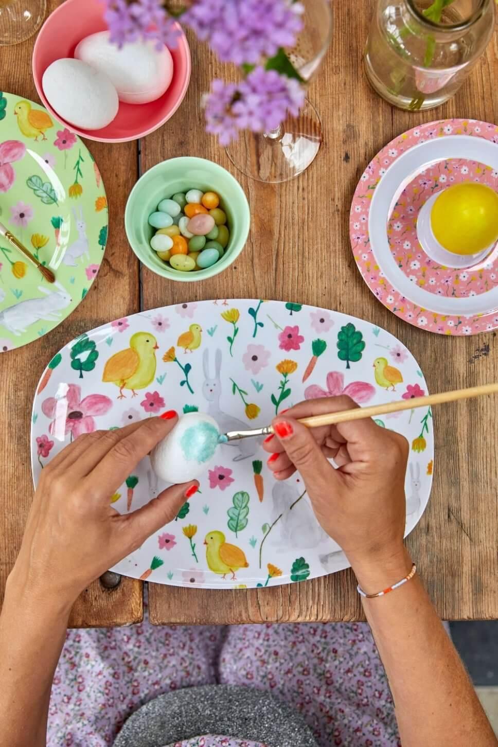 Frau bemalt Ei an österlich dekoriertem Tisch mit buntem Geschirr