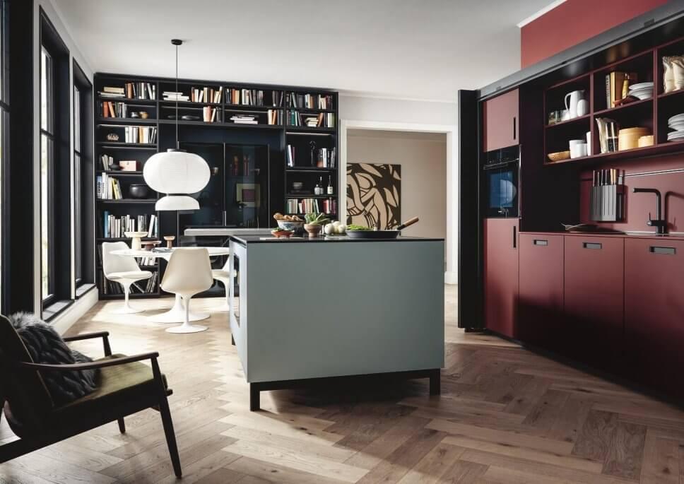 Moderne offene Küche mit Kochbereich hinter geöffneten Falttüren, Kücheninsel und Esstisch