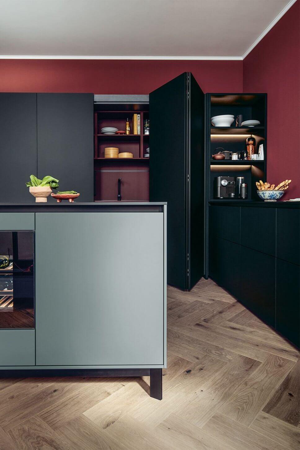 Moderne offene Küche mit Kochbereich hinter geöffneten Falttüren und Kücheninsel