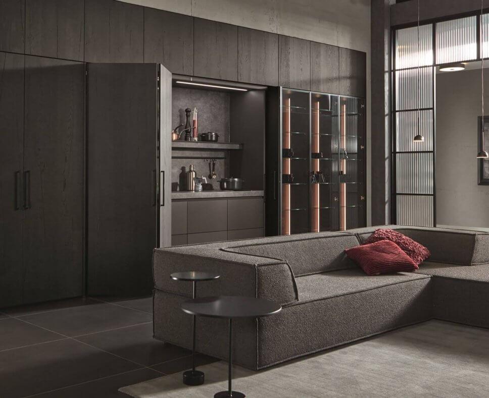 Moderne offene Küche mit Kochbereich hinter geöffneten Falttüren, Vitrine und Sofa