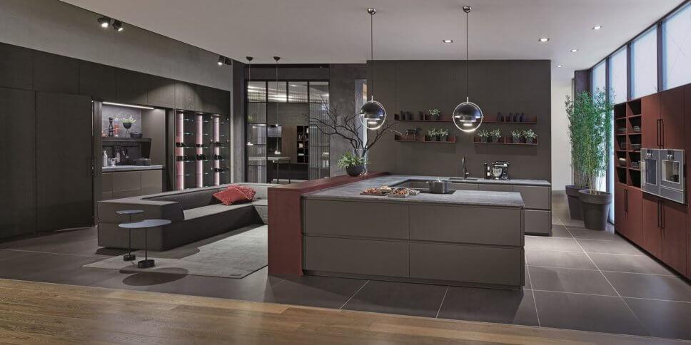 Moderne offene Küche mit Kochbereich hinter geöffneten Falttüren, Kücheninsel und Sofa