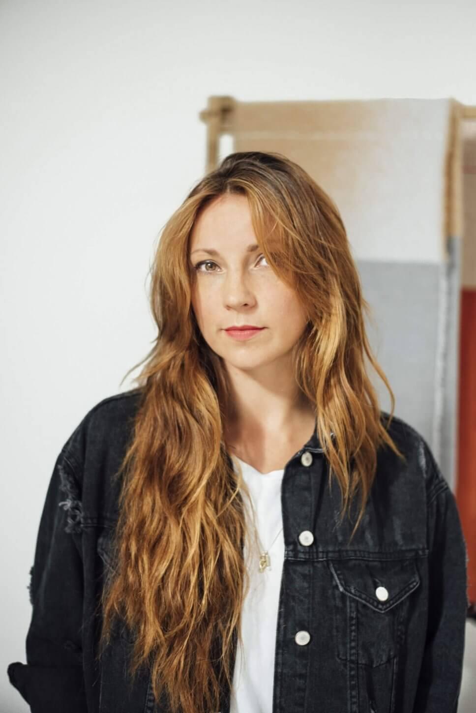 Textildesignerin Mae Engelgeer vor einem Wandteppich