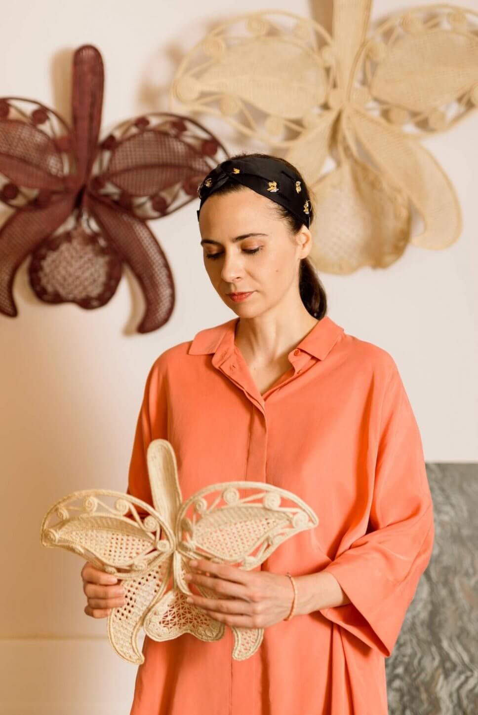 Designerin Cristina Celestino hält ihren aus kunstvoll in Blütenform aus Geflecht gefertigten Wandschmuck in den Händen