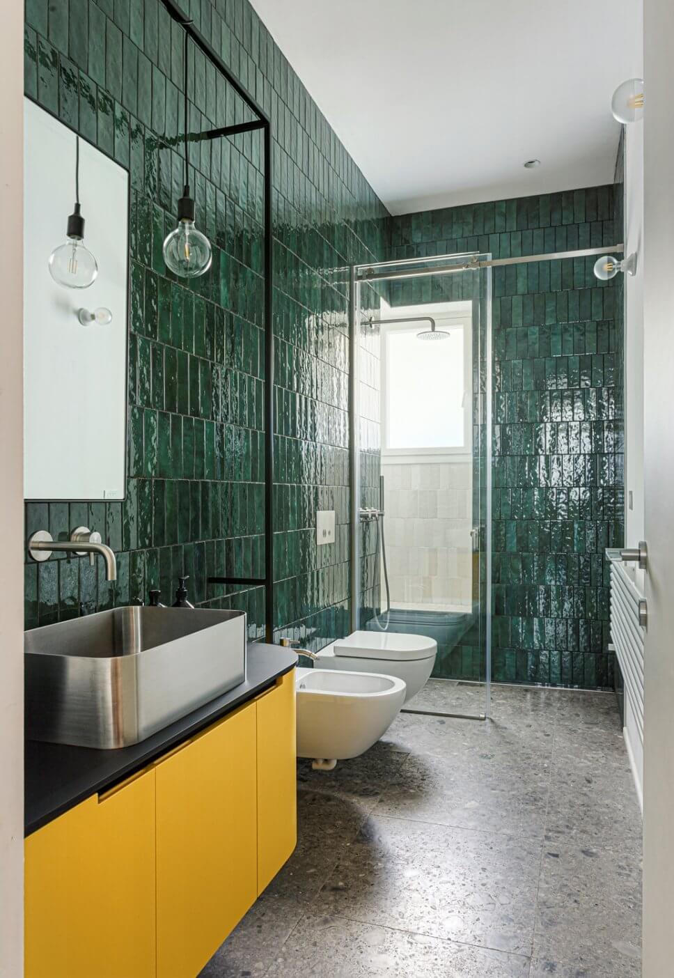 Großes Modernes Duschbad mit Kassettenfronten, gelben Schränken, offener Dusche, Wandtoilette, grünen Fliesen, Keramikfliesen, grüner Wandfarbe, Marmorboden, Aufsatzwaschbecken, Laminat-Waschtisch, grauem Boden und schwarzer Waschtischplatte in Mailand